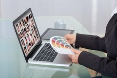 Photo editor using laptop at desk Royalty Free Stock Photography