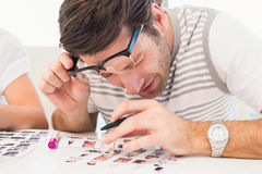 Photo editor using a magnifying loupe Stock Photos