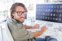 Photo editor viewing thumbnails on computer and turning for port Royalty Free Stock Images