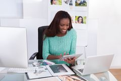 Photo editor working at office desk. Happy African American female photo editor working at office desk royalty free stock photo