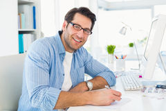Photo editor writing on a paper while looking at camera Royalty Free Stock Image