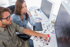 Photo editors choosing thumbnails for final cut. At their desk Stock Images