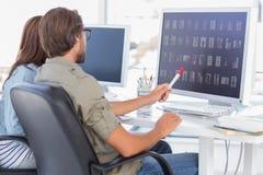 Photo editors choosing thumbnails. On screen at their desk Royalty Free Stock Image