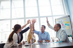 Photo editors high-five in meeting room Stock Photography