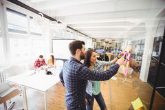 Photo editors looking at sticky notes on glass in meeting room royalty free stock image