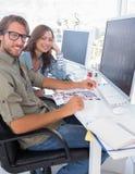 Photo editors smiling at camera. Sitting at their desk Stock Photos