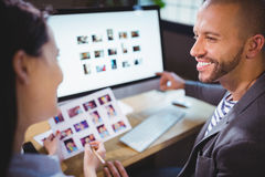 Photo editors smiling while discussing over computer Stock Photos