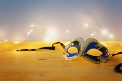 Photo of elegant venetian, mardi gras mask over wooden table and garland gold lights. Photo of elegant venetian, mardi gras mask over wooden table and garland