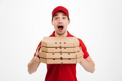 Photo of emotional guy from delivery service in red t-shirt and. Cap holding stack of pizza boxes isolated over white background Royalty Free Stock Image