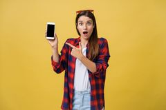 Photo of emotional shocked young pretty woman standing isolated over yellow background using mobile phone looking aside. stock photos