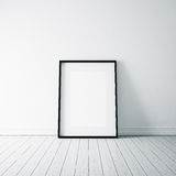 Photo of empty frame on the white floor. Vertical. White blank frame on the white wooden floor and white wall on the background stock photo