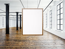 Photo of empty interior in modern loft. Open space loft.Empty white canvas hanging on the wood frame. Wood floor, bricks. Photo of empty interior in modern loft Royalty Free Stock Image