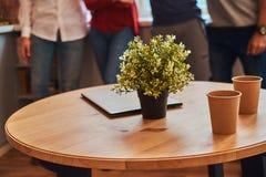 Photo en gros plan d'un ordinateur portable, de deux tasses de papier et de fleur sur une table dans le dortoir d'étudiant photographie stock
