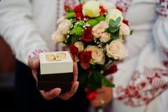 Photo en gros plan d'une boîte avec des anneaux dans la main du ` s de marié et un bouquet Photographie stock libre de droits