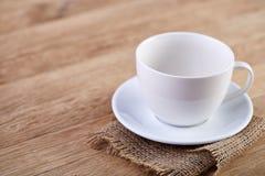 Photo en gros plan de foyer sélectif de tasse de thé et de soucoupe blanches vides sur le fond rustique de vintage avec la servie Images libres de droits