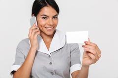 Photo en gros plan de jeune domestique heureuse dans l'uniforme gris parlant de s photos libres de droits
