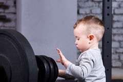 Photo en gros plan de petit garçon avec le barbell contre le mur de briques dans le gymnase convenable de croix Photographie stock