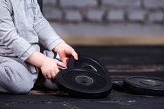 Photo en gros plan de vue de petit enfant sportif avec le barbbell contre le mur de briques au gymnase convenable de croix Photographie stock