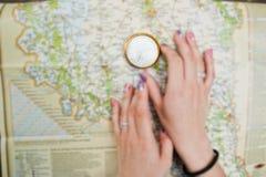 Photo en gros plan des mains femelles avec la boussole sur une carte photo libre de droits