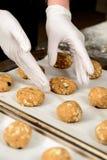 Photo en gros plan des mains mettant les biscuits savoureux sur un plateau de cuisson Photographie stock libre de droits