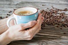 Photo en gros plan qu'une tasse de café parfumé dans un ` s de femme remet sur un fond des grains de café sur la table en bois image stock
