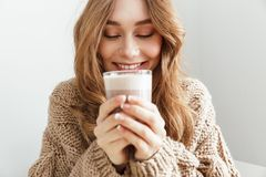 Photo of european attractive woman 20s drinking glass of latte,. Photo of european attractive woman 20s drinking glass of latte and enjoying taste of coffee royalty free stock photo