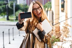 Photo of european woman 20s holding laptop and using smartphone in city street. Photo of european woman 20s holding laptop and using smartphone while walking stock images