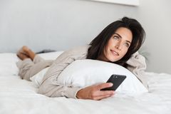 Photo of european woman 30s using mobile phone, while lying in bed with white linen in bright room stock photo