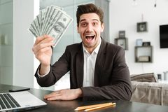 Excited young businessman showing money using laptop computer. Photo of excited young businessman in home indoors. Looking camera showing money using laptop Royalty Free Stock Images
