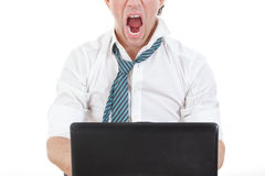 Photo of exhausted, angry and overworked half face business man. With laptop in front him on office desk at his work Stock Photos