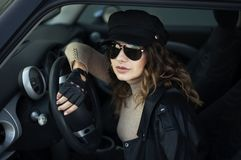 Photo extérieure de mode de femme avec les cheveux foncés dans la veste en cuir noire et des lunettes de soleil posant dans la ré photo stock