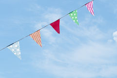 Photo of fabric bunting, flags, over slue sky with clouds. Stock Image