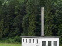 Forest and factory. Photo of a factory building sitting in front of a huge forest background Royalty Free Stock Images