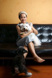 Photo of family. A woman is sitting on sofa with her lovely pets Royalty Free Stock Photography