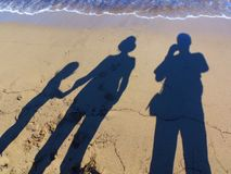 Family Memory. Photo of family shadows on a sea beach. Abstraction symbolizing memories of a long time ago royalty free stock photo