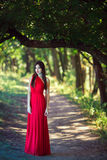 Photo of fashion woman in red dress in fairy forest. Beauty springtime royalty free stock photography
