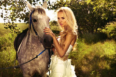 Beautiful blonde lady with posing with horse. Photo of fashionable beautiful blonde woman posing with horse in green garden Royalty Free Stock Images