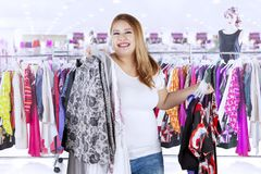 Fat woman buying clothes in the boutique. Photo of fat woman looks happy while buying new clothes while standing in the boutique Stock Photo