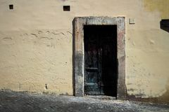 Black burnt door, contrasting with it`s pale peach walls and aged frame, in Rome Italy Royalty Free Stock Photo
