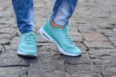 Photo of feet in new fashionable sneakers while having a walk in city urban street style life slifestyle denim Photo of feet in ne royalty free stock photo