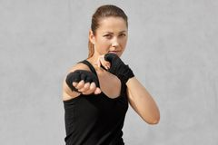 Photo of female boxer in defensive stance, looks fierce, dressed in black t shirt, bandages on hands, ready to fight with opponent royalty free stock photos