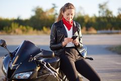 Photo of female driver holds smart phone in hands, surfes bikers blog in internet, wears stylish clothes, leans at black fast moto royalty free stock image