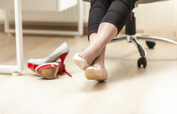 Photo of female feet in ballet in office Royalty Free Stock Photo