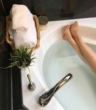 Photo of female feet in bathtub. Photo of female feet on the edge of the bathtub with a basket of towels and plant royalty free stock photography