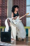 Photo of a female guitarist playing an electric guitar. Royalty Free Stock Images