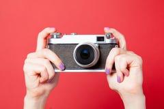 Photo of female hand holding retro camera on the wonderful red b royalty free stock photo