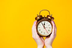 Photo of female hands holding alarm clock on the wonderful yello Royalty Free Stock Images