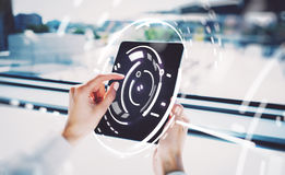 Photo of female hands touching screen Of tablet, visual interfaces effects. Blurred background. Stock Photo