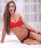 Photo of female model lying in red lingerie on bed Royalty Free Stock Photos