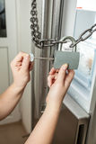 Photo of female opening lock with chain on refrigerator Royalty Free Stock Images